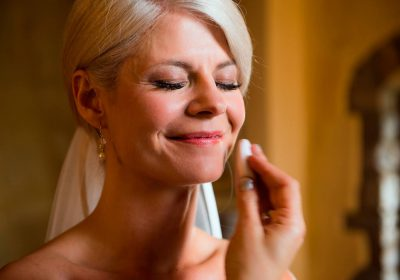A smiling bride getting her make up done by a member of Consuelo's team